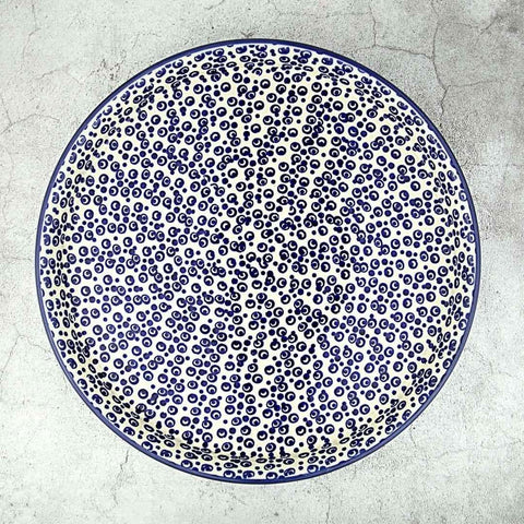 Polish pottery hand-decorated round platter with blue bubble design seen from above