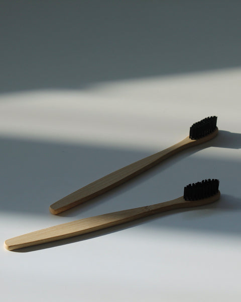 Eco friendly, black Bamboo Toothbrush laying in natural light | Jentl.com.au