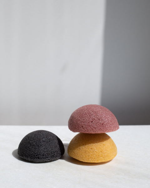A stack of Konjac Sponges, 100% natural pink yellow and black cleansing tool | 'JENTL