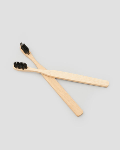 A pair of Bamboo Toothbrushes with black bristles, A sustainable alternative to plastic | 'JENTL
