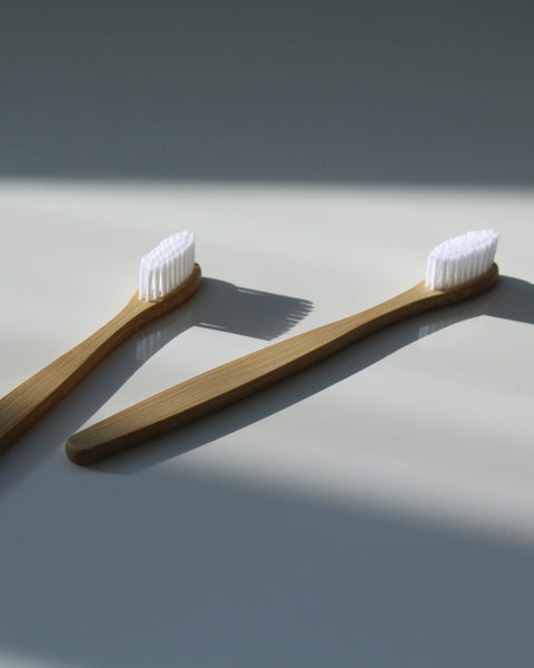 Two White Bamboo Toothbrushes Laying in Natural Light | Jentl.com.au