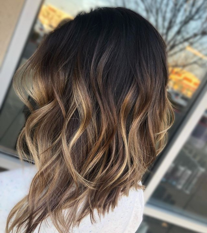 Person with a dark long bob with blonde balayage