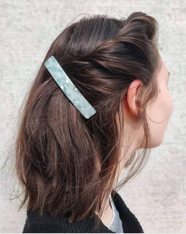 White woman with dark brown hair pinned with a turquoise hair clip