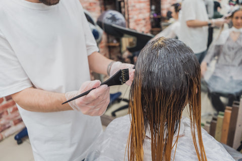 Woman with light brown ombre hair coloring her hair at a salon