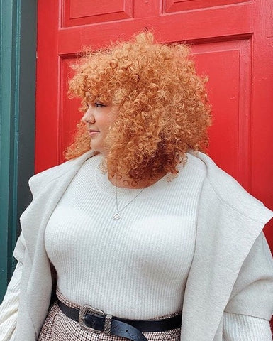 A white woman with tight red curls in front of a red door
