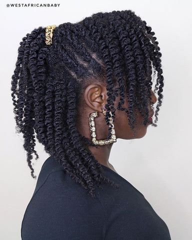 A Black woman wearing a twist-out in a half-up, half-down hairstyle with gold earrings