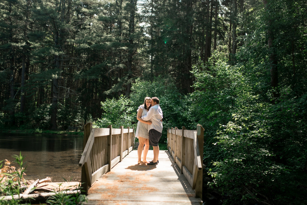 husband and wife standing on a bridge hugging