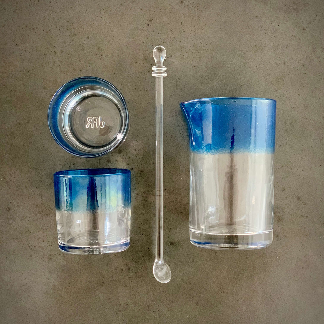 The Mariner Cocktail Set - Alined in a grid, composed of one cocktail mixing glass, one spoon, and two rocks glasses with an ocean blue band of color.
