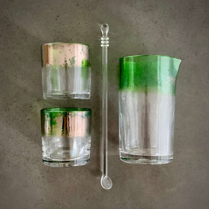 The Naturalist Cocktail Set - Alined in a grid, one mixing glass, one spoon, and two rocks glasses, all with a bright emerald green band of color.