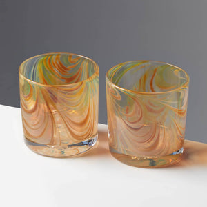 Pair of Oak Grain style cocktail glasses with amber and tan swirls against a contrasting gray background.