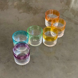 Set of 6 cocktail glasses in a striped ROYGBV rainbow color pattern, lined up in an S curve.