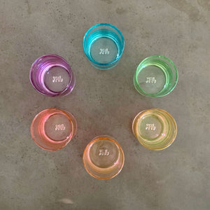 Set of 6 cocktail glasses in a ROYGBV rainbow color scheme. Each glass is one solid color. Aerial view of cups in circular color wheel.