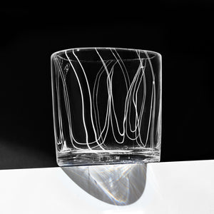 Simpatico in White rocks glass with vertical fine white lines against a dramatic black background.