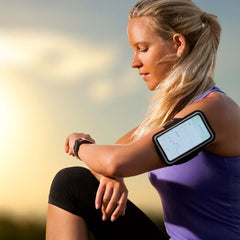 Portrait of a young woman taking a break during her run and checking her smart watch.