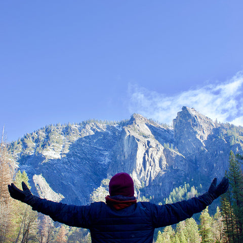 A person with their arms outstretched towards the mountains.