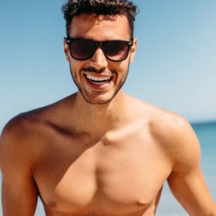 A shirtless young man wearing sunglasses smiling and standing at the beach with the ocean in the background.