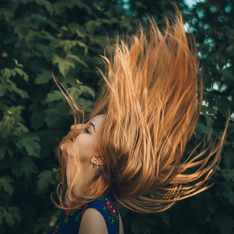 A woman flinging her hair into the air.