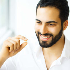 A handsome young man holding a zinc pill and smiling.