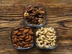 walnuts, almonds, and cashews in bowls on wooden table