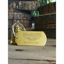 "Load image into Gallery viewer, brass bell made of a .50 cal shell with brass tag that says ""Eat, Sleep, Ride"""