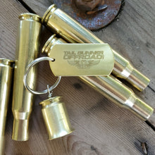"Load image into Gallery viewer, brass bell made of a .50 cal shell with brass tag that says ""Have fun & stay safe"""