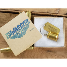"Load image into Gallery viewer, packaging for brass bell made of a .50 cal shell with brass tag that says ""Just Empty Every Pocket"""