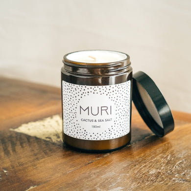 unlit cactus and sea salt white candle in amber jar with white Muri logo on wooden table