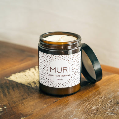 unlit christmas morning white candle in amber jar with white Muri logo on wooden table