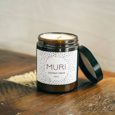 unlit white candle inside amber jar with white branded label