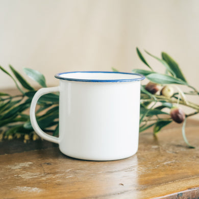 white empty enamel mug on wooden table