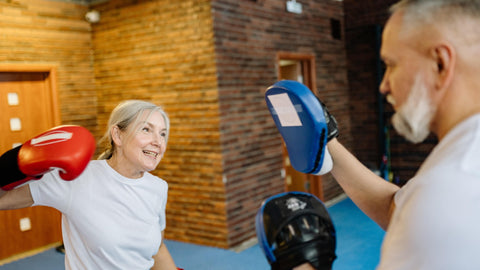 Older Woman With Boxing Gloves Striking Pads Held By Older Man