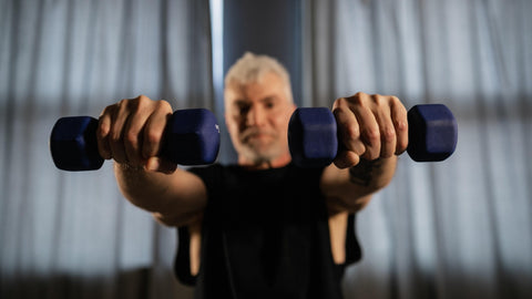 Older Man With Grey Hair Holding Two Dumbbells Towards The Camera