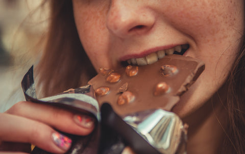 Woman eating chocolate bar product snack