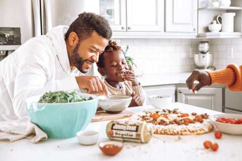 Happy father and son preparing food in kitchen at home