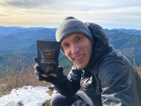 Man holding GRIT Performance Chocolate Bites with mountains in background