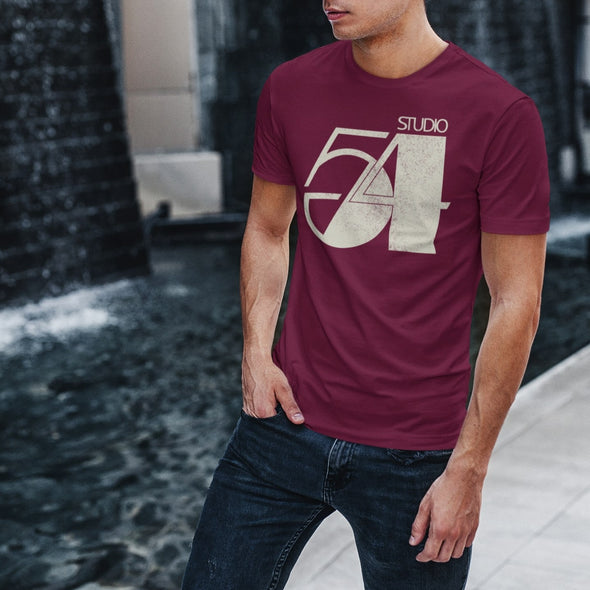 Man posing in the street with hand in jeans pocket wearing a claret t-shirt with 'Studio 54' logo print in cream.