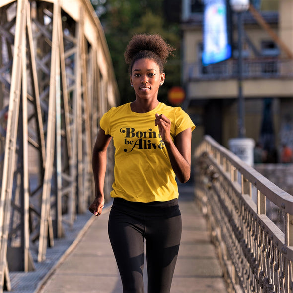 Young black women joggin across a bridge in yellow 'born to be alive' t shirt.
