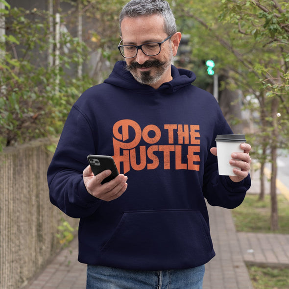 Bearded man looking at phone in tree lined street wearing a navy hoodie with 'Do The Hustle' orange slogan print.