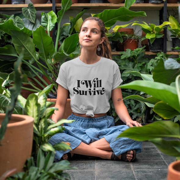 Girl meditating in greensouse wearing a grey t-shirt with 'I Will Survive' slogan print in black.