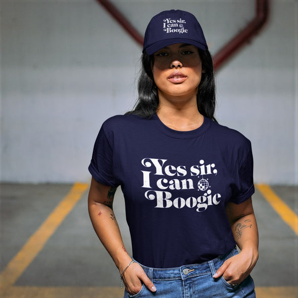 Woman in underground parking lot wearing navy hat and t-shirt with 'yes sir i can boogie' slogan in white.