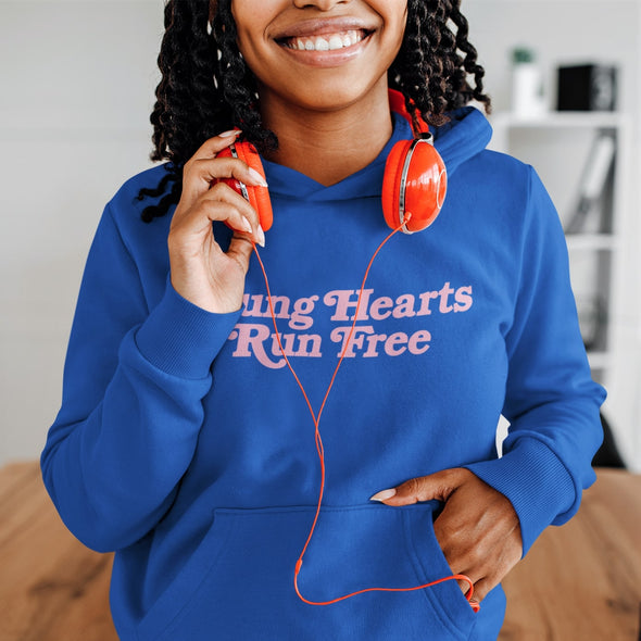 Young Woman wearing Classic Royal Blue Hoodie with Retro-Style text 'Young Hearts Run Free' printed on chest in Pink