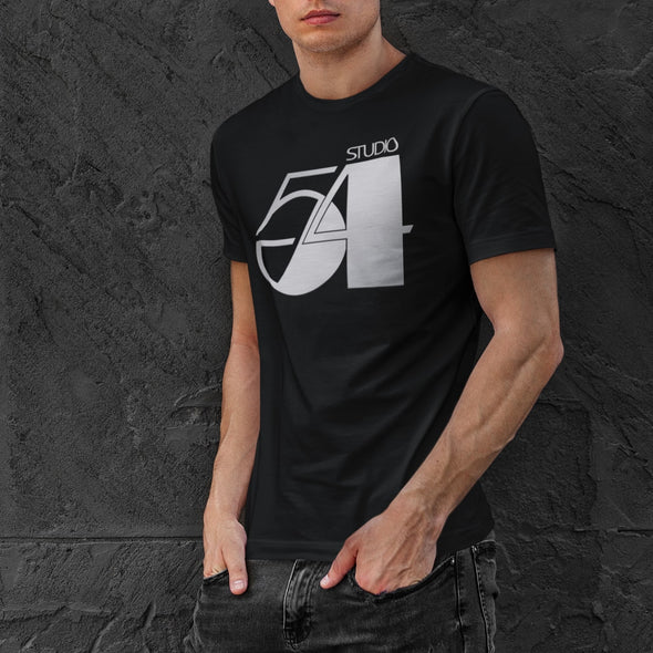 Young man posing against a stone wall wearing a black t-shirt with a 'Studio 54' design in silver.