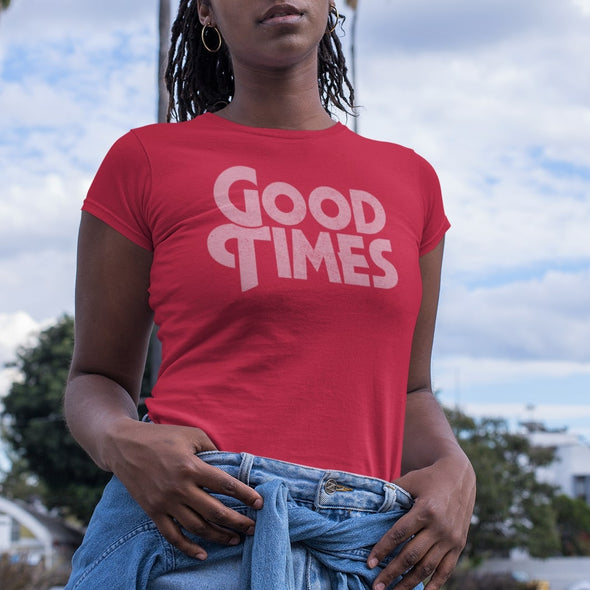 Young black women posing with hands on hips wearing a 70s style red t-shirt with a pink coloured 'Good Times' vintage style slogan.