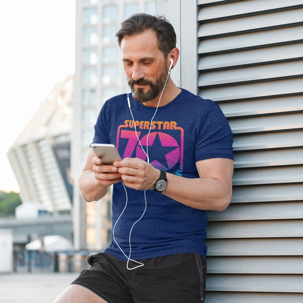 Man wearing royal blue t shirt with seventies retro graphic listening to music.