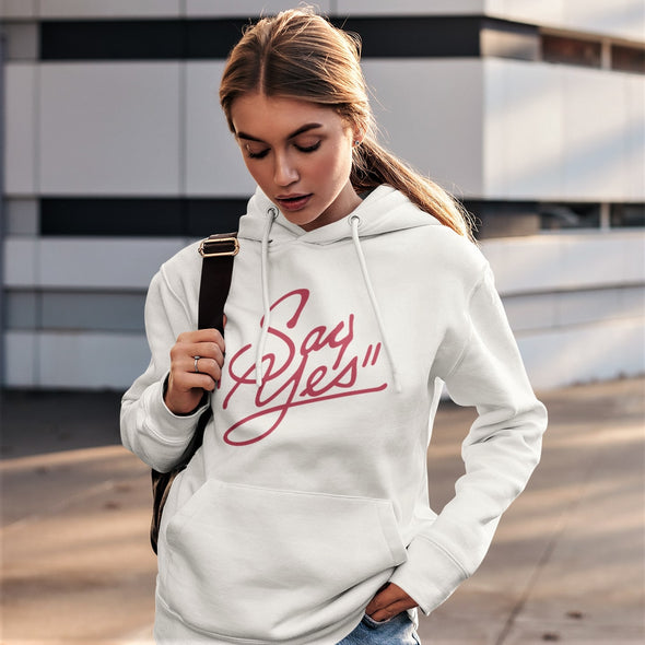 Young women in an urban setting wearing a white hoodie with bright red 'Say Yes' retro slogan.
