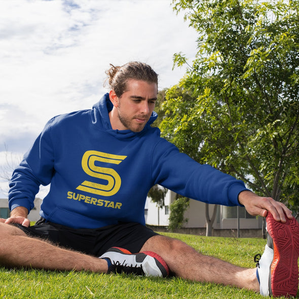 Sporting man stretching on grass wearing a hoodie with retro 'Superstar' slogan in bright yellow.