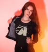 Stunning brunette modelling an open jacket to reveal a black t-shirt with 'Studio 54' retro logo in stone white colour.