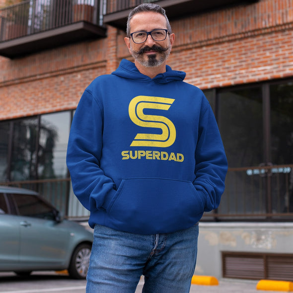 Middle age man smiling in street wearing a blue hoodie with a retro giant 'S' print in yellow.