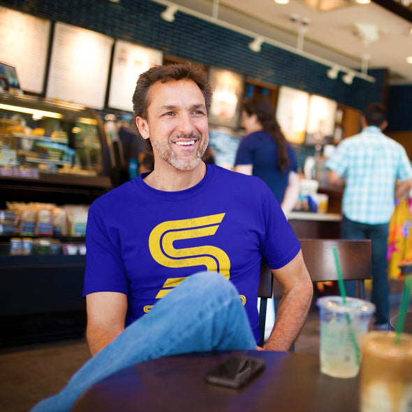 Middle age man sat smiling in a cafe wearing a blue tee with bright yellow 'Superdad' slogan design.