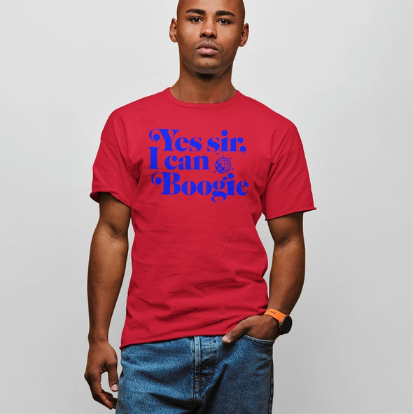 Handsome young black guy with hand in his jean pocket posing with a red t-shirt which has a 1970s slogan in bright blue' Yes Sir i Can Boogie'.